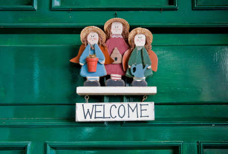 Welcome sign hanging at green doors.