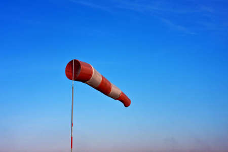 Windsock in airfield showing wind strength on blue sky background. photo