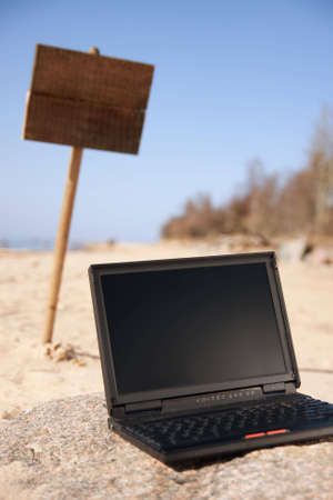 One black laptop and wooden sign in background alone at beach. Stock Photo - 4802015