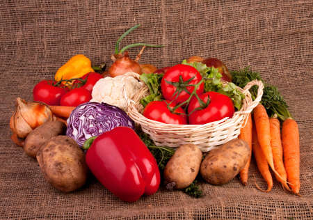 Pile of various vegetables on linen fabric. Three tomatoes in basket, carrots, paprika, potatoes, onions. photo