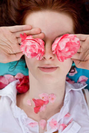 Young woman holding flowers in hands in front of eyes. She is looking through flowers. Some petals laying on her neck. White blouse.  photo