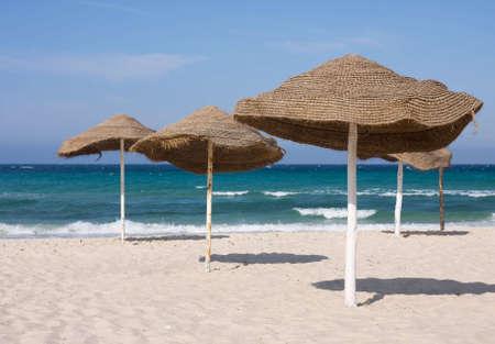 sunshades: Four sunshades on empty beach in Tunisia Stock Photo