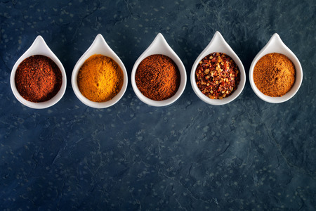Different spices in tasting spoons on dark slate from above Standard-Bild