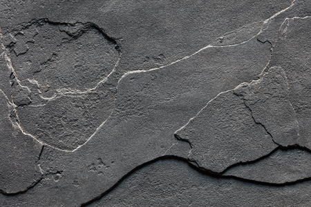 Natural Layered Rough Slate Stone Background Texture in dark grey colour
