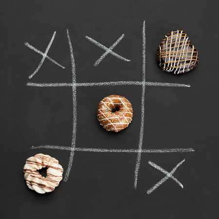 Noughts and Crosses on black board with Dougnuts Standard-Bild