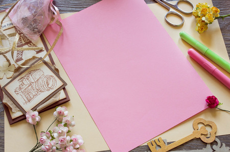card making: Top view of  paper roses and a pink sheet of paper. Making handmade cards Stock Photo