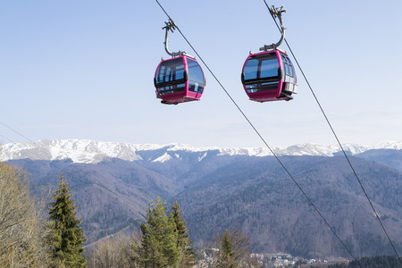 climbing cable: Two cable cars climbing to a ski resort up in the mountains