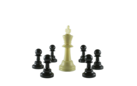 White king surrounded by the black pawns in a circle formation photo