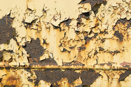chipped: Chipped layer of yellow paint on rusty metallic surface, background