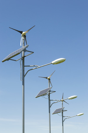 Row of three street lighting poles using alternative energy as power source in the form of a solar panel and small wind turbine photo