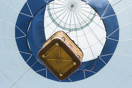 Suspended hot air balloon with passenger carrying basket viewed from below photo