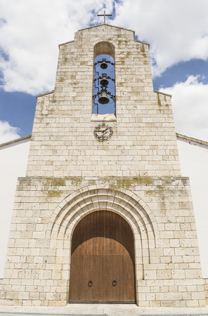 overlapped: Old catholic church entrance with three overlapped bells and iron clock attached to the wall