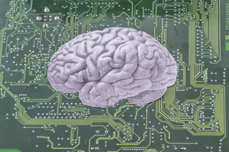 neuronal: Depiction of a human brain placed over a printed circuit board, as a concept of the fast growing field of artificial intelligence