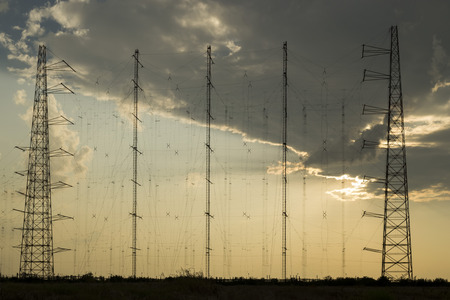 Array of radio communication antennas on cloudy sky , at sunset photo