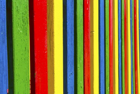 laths: Wooden colored laths in vibrant red, blue, green and yellow of a playground fence