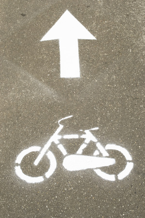 sprayed: Freshly painted bicycle sign sprayed on asphalt with forward arrow indicating direction