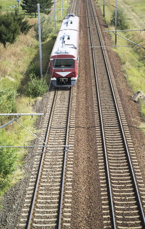 approaching: Aerial view of an incoming train with two passenger cars on an electrified railway route