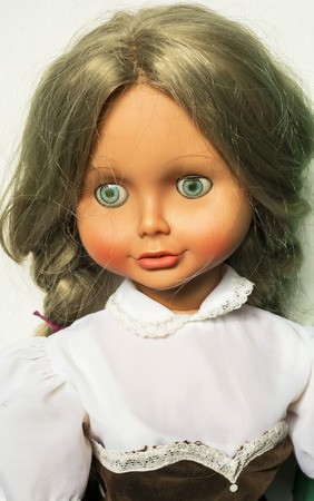 velvet dress: Portrait of a doll with blond hair, blue eyes dressed in laced white shirt and brown velvet dress Stock Photo