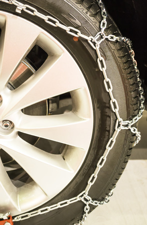 the height of a rim: Winter tire  equipped with metal chain around it for better road grip in winter time conditions Stock Photo