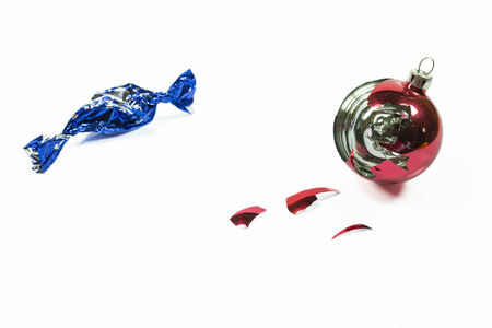 Christmas red glass ball broken with scattered shards and blue empty candy wrapper, on white photo