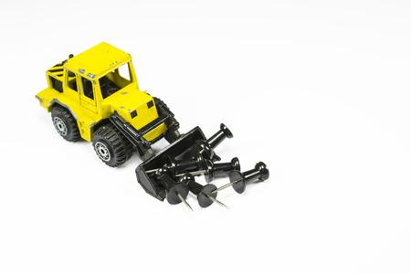 cargador frontal: Maqueta juguete cargadora frontal con el cuchar�n delantero lleno de alfileres de oficina, en el fondo blanco Foto de archivo