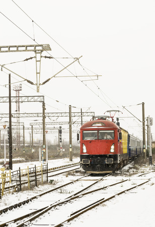 buffers: Passenger train approaching the railway station on winter conditions, while snowing Stock Photo
