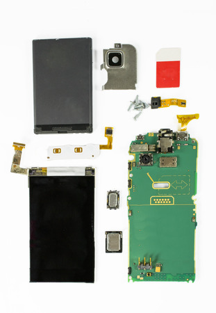 miniaturization: Modern smart phone dismantled with main electronic components displayed together against a white background Stock Photo