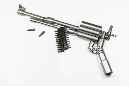 rounds: Machine gun improvised from tubular keys, extenders, articulated joints and bits set serving as rounds, isolated on white