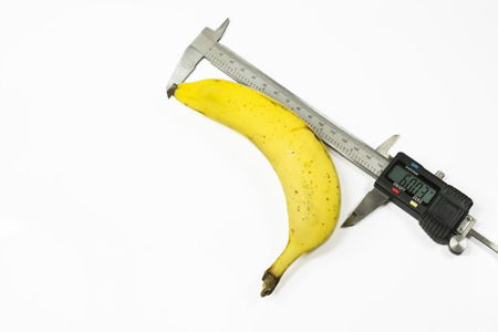 movable jaw: Banana fruit measured in length with a digital caliper , on white background