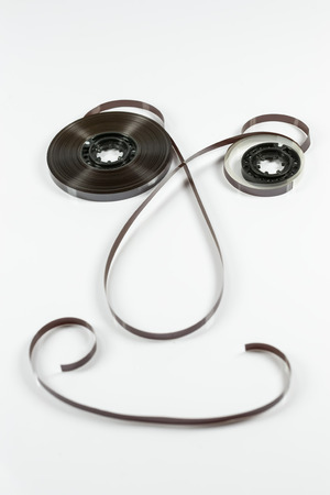 resemblance: Magnetic tape and plastic rollers from an audio cassette arrange as to resemble a smiling human face