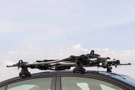 traverse: Bicycle carrier system mounted on the roof of a car against a blue sky background