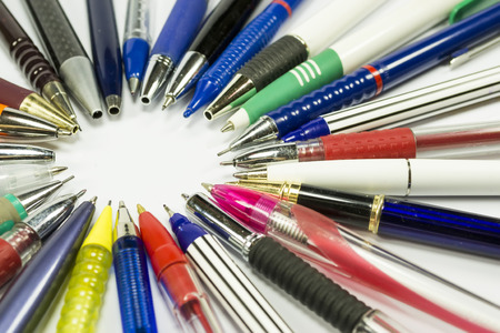 inwards: Ballpoint pens and mechanical pencils of various shapes and colors with their tip oriented inwards, forming a circle
