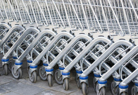interlocked: Metallic shopping carts of a supermarket interlocked in a row for space saving Stock Photo