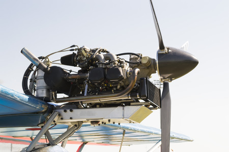 carburettor: Exposed airplane engine with three blades propeller  mounted on the upper wing