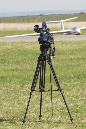 tripod mounted: Tripod mounted video camera oriented towards a stationary glider on an airfield