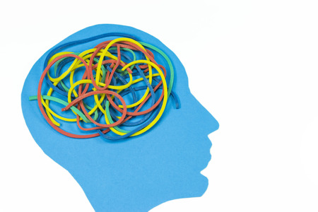 Blue shape of a human head with tangled colored elastic bands  concept for complexity of the human mind