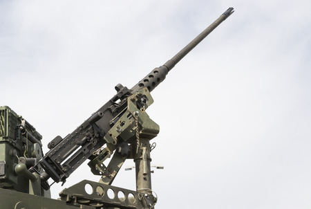 tripod mounted: Modern military machine gun tripod mounted on mobile platform aiming at the sky