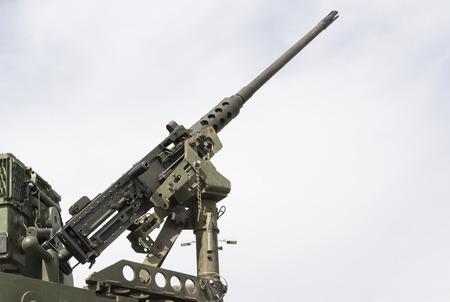 tripod mounted: Modern military machine gun tripod mounted on mobile platform aiming at the sky