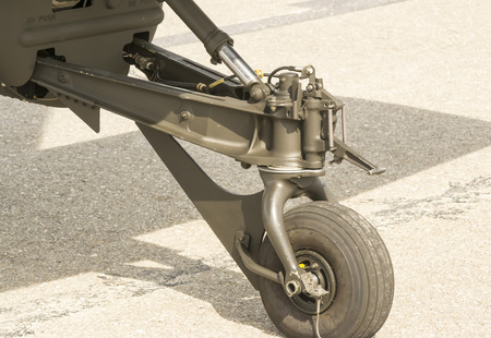 grounded: Rear landing gear of a modern attack helicopter stationed on an airfield