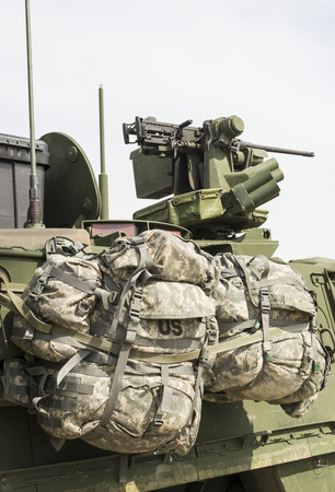 belonging: Two rucksacks currently belonging to U.S. army personnel attached to the side of an armored field vehicle Stock Photo