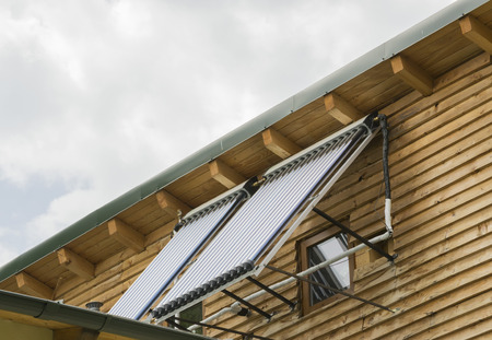solar heating: Two panels mounted side by side on the exterior wall of a house for water heating using solar energy conversion