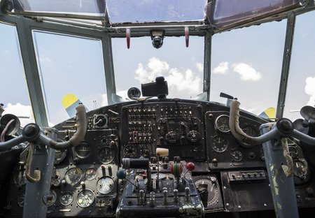 throttle: Vintage airplane cockpit interior with blue sky and white clouds in the background