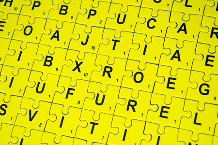 cypher: Connected yellow puzzle pieces with letters imprinted on them, background