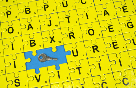 concealment: Connected yellow puzzle pieces with letters , two of them missing and a key , on blue background