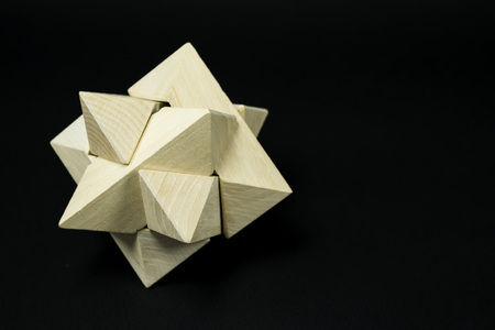 three dimensional shape: Wooden puzzle from carved tiles combined to form a complex star like three dimensional shape, on black background