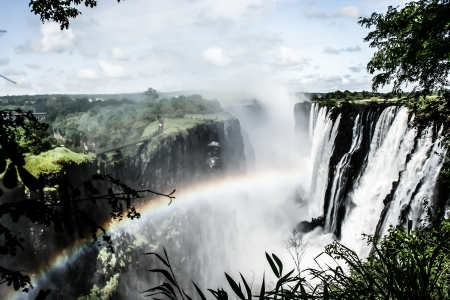 zambia: Rainbow over Victoria Falls on Zambezi River, border of Zambia and Zimbabwe  ( HDR image ) Stock Photo