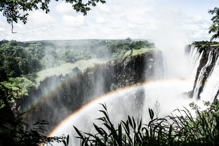 Rainbow over Victoria Falls on Zambezi River, border of Zambia and Zimbabwe  ( HDR image ) Stock Photo