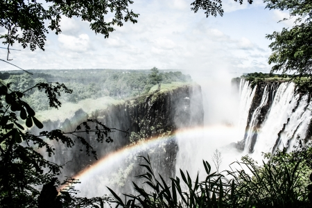 zambezi: Rainbow over Victoria Falls on Zambezi River, border of Zambia and Zimbabwe  ( HDR image ) Stock Photo