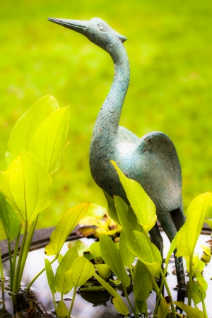 Heron fountain in green background photo