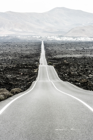timanfaya: Empty road crossing an arid mountain, Lanzarote, Canary islands, Spain  Stock Photo